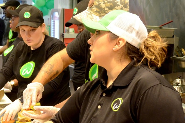 Kendra Jackson, Army spouse of 11 years and new general manager of Wahlburgers in the Kaiserslautern Military Community Center, works the food line during the lunch rush hour the second day of operation for the new restaurant.