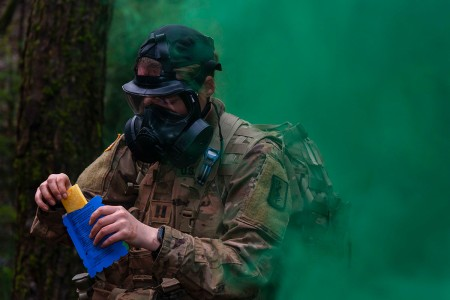 Army Capt. Collenn O'Conner follows contamination procedures during a simulated chemical attack as part of an Expert Field Medical Badge test in Baumholder, Germany, Dec. 16, 2019.