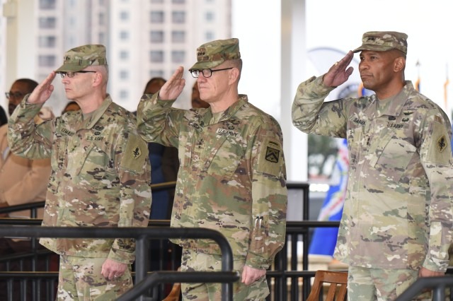 Major General Dennis P. LeMaster, Lieutenant General James E. Rainey, and Major General Patrick D. Sargent salute the national colors during the playing of the national anthem.