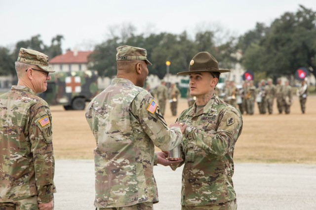While LTG James E. Rainey looks on, Drill Sergeant David Nagel, the MEDCoE Best Medic of the Year, presents MG Patrick D. Sargent the shell from the last round of salute as a memento of the change of command ceremony.