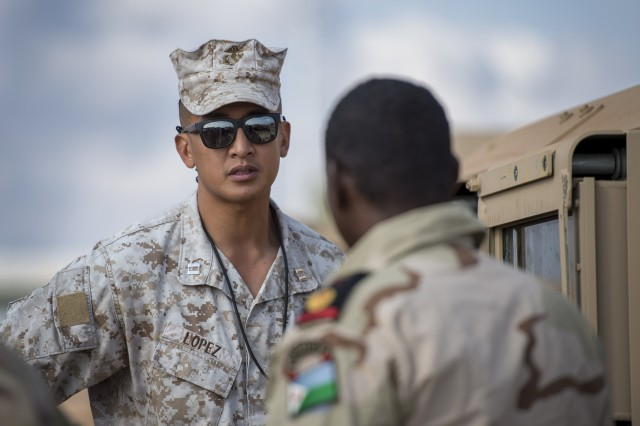 U.S. Marine Corps Capt. Adrian Lopez, Rapid Intervention Battalion (RIB) project officer assigned to CJTF-HOA, discusses the capabilities of a Humvee's engine with Djiboutian Armed Forces Maj. Mohamed Assoweh, RIB commander, during the delivery of the Humvees to the RIB outside Djibouti City, Djibouti, on Dec. 26th. The U.S. delivered 54 Humvees to the RIB as part of a $31 million train-and-equip partnership between the U.S. government and the Djiboutian military. (U.S. Air Force Photo by Senior Airman Codie Trimble)