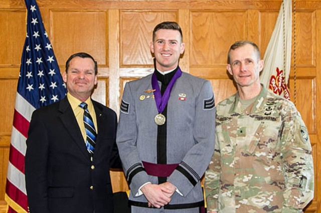 Dave Jones, MX400 instructor at the Simon Center for the Professional Military Ethic, Class of 2019 Cadet Camm Johnson (center) and Commandant of Cadets Brig. Gen. Curtis A. Buzzard after Johnson received the Lt. Gen. Robert Foley Scholarship of Honor Medallion Dec. 19.