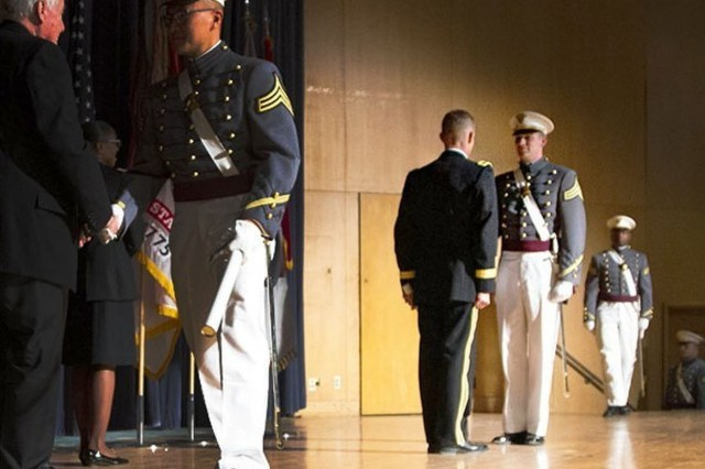 Commandant of Cadets Brig. Gen. Curtis A. Buzzard presides over the ceremony and hands out diplomas as members of the 50-year affiliate class, USMA Class of 1969, provides the second lieutenant bars to the new officers.