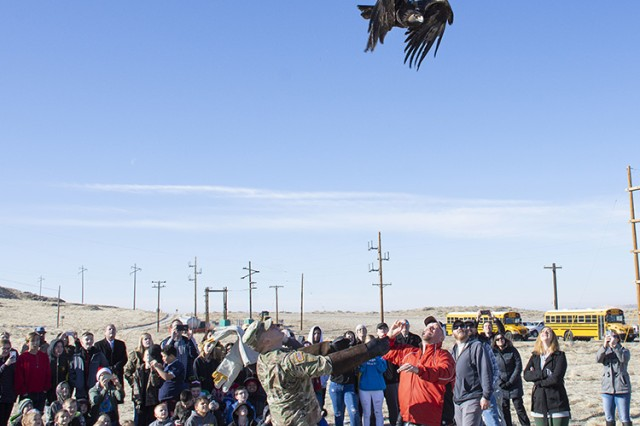 While Dugway K-12 School children, teachers and administrators of Tooele County School District look on Dec. 19, 2019, Army Sgt. Zachary Dunn (left) and Resources Manager Robbie Knight (red jacket), release a rehabilitated golden eagle to the wild.