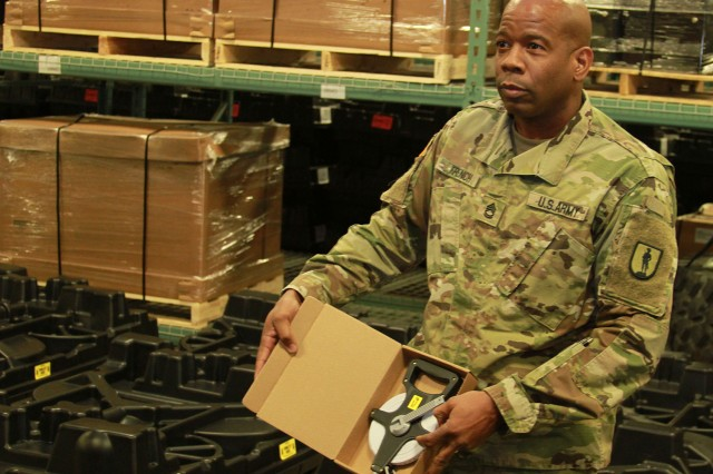 Displaying a measuring tape so that it can be inventoried is Sgt. 1st. Class Ronald French from the Michigan National Guard.