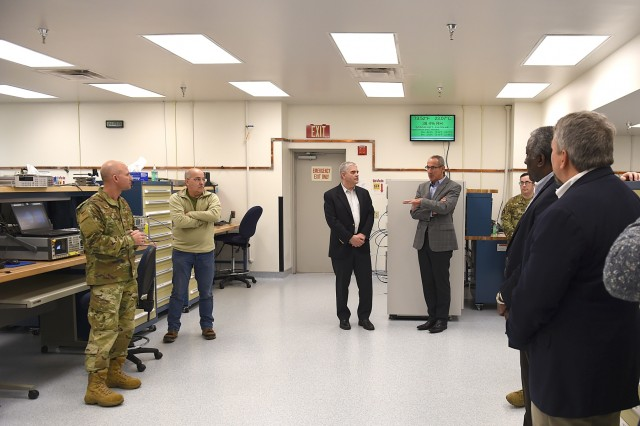 Col. Eliot Sasson, 62nd Maintenance Group commander, far left, speaks with members of the National Commission on Military Aviation Safety inside the precision equipment measurement lab on Joint Base Lewis-McChord Jan. 7.