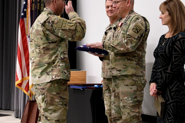 Sgt. 1st Class Matthew Tucker presents Lt. Gen. Michael Lundy with the flag of the United States during Lundy's retirement ceremony Jan. 8, 2020 in DePuy Auditorium, Fort Leavenworth, Kan. Lundy was the Combined Arms Center commanding general from May 2016 to Dec. 16, 2019. Photo by Tisha Swart-Entwistle, Combined Arms Center Public Affairs Office.