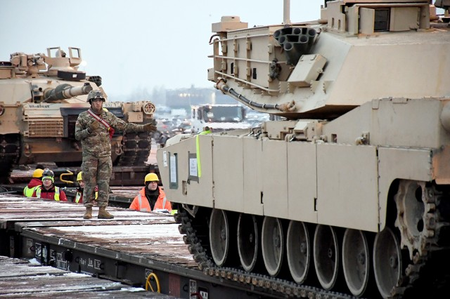 A Soldier guides a tank assigned to 1st Armored Brigade Combat Team, 1st Infantry Division, as it's loaded on board a railcar at Port of Antwerp, Belgium, Jan. 24, 2019. The unit deployed to Europe in support of Operation Atlantic Resolve.