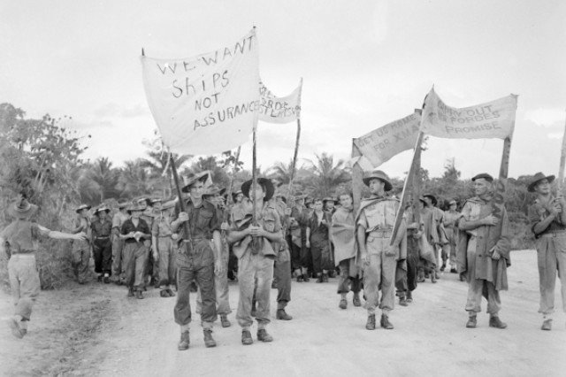 """Nearly 4,500 Australian soldiers carry banners during a five-kilometer march to protest long demobilization waits on the island of Morotai, Indonesia, Dec. 10, 1945. The protest event is known as the """"Morotai Mutiny."""""""
