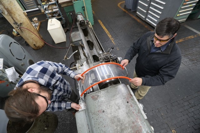 Machinist apprentice Jason Nixon, left, test fits the installation of a machine guard with Safety Specialist Greg Schlotter. The guard is part of Watervliet Arsenal's machine guarding program designed to increase user safety on older equipment.