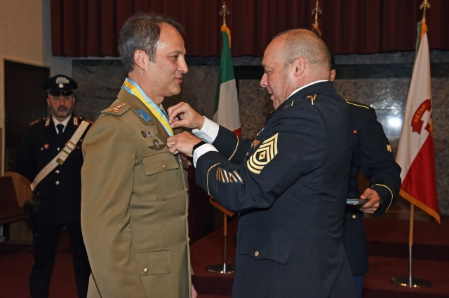 """U.S. Army Soldier Master Sgt. Melvyn Lopez, right, presents the National Infantry Association """"The Martyrdom of Saint Maurice"""" Medal to the outgoing Deputy Chief of Staff of United States Army Africa and Senior Italian Officer Colonel Umberto D'Andria, during the Designation of Responsibility Ceremony at Caserma C. Ederle in Vicenza, Italy, January 16, 2020. (U.S. Army Photos by Paolo Bovo)"""