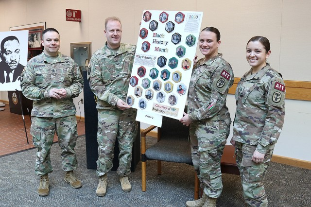 Madigan Army Medical Center Commander Col. Thomas Bundt and Command Sgt. Maj. Victor Laragione help representatives of the radiology specialist advanced individual training class present their winning poster at Madigan's Martin Luther King, Jr. Day observance on Jan. 16.