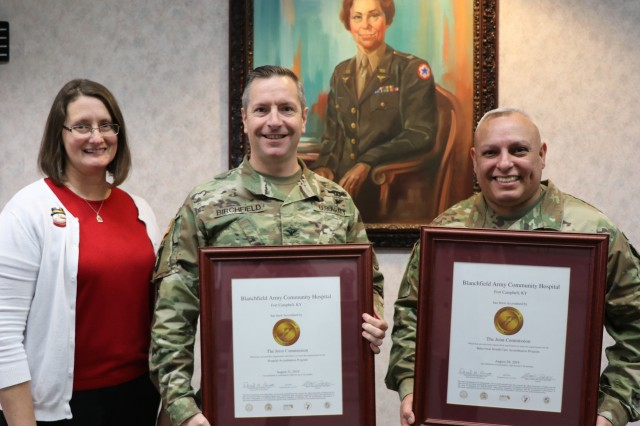BACH Accreditation Manager, Ms. Quetta Beck, Hospital Commander, Col. Patrick T. Birchfield, and Hospital Command Sergeant Major, Command Sgt. Maj. Daniel Santiago, proudly display the hospital's Gold Seals of Approval from The Joint Commission. The Joint Commission accredits and certifies more than 22,000 health care organizations and programs in the United States. BACH underwent a rigorous, unannounced onsite review late last year for hospital accreditation and behavioral health program accreditation, earning the Gold Seal of Approval for both. U.S. Army photo by Maria Yager.