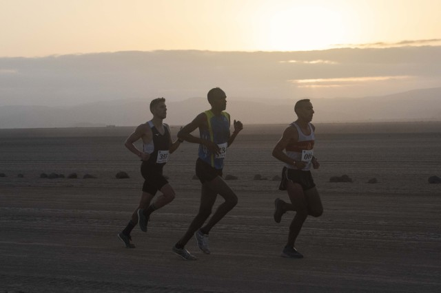 Participants of the Grand Bara Race run along the 15k trail as the sun rises over the Grand Bara Desert, Djibouti, Jan. 15, 2020. Participants followed a 15-kilometer line of rocks, originally placed by the French Foreign Legion. (U.S. Air Force photo by Tech. Sgt. Ashley Nicole Taylor)