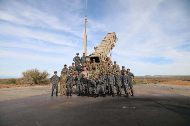 Patriot missile crews from 11th Air Defense Artillery Brigade and Japanese Air Self-Defense Force assemble for a group photo on an M901 Launching Station after the successful completion of Operation Shining Star, Nov. 9, 2019.  Operation Shining Star was a successful tri-national Patriot missile system live-fire exercise to improve interoperability and joint training held at McGregor Training Complex, Fort Bliss, Texas. (U.S. Army photo by Sgt. Mariah Jones, 11th ADA BDE)