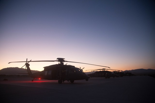 UH-60 Black Hawk helicopters from the Joint Aviation Command, United Arab Emirates, await flight crews on a tarmac within the National Training Center prior to the start of an air assault mission during Decisive Action Rotation 17-09, Sept. 21, 2017.  (U.S. Army photo by Sgt. David Devich, Operations Group, National Training Center)