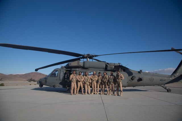 Aviators and crew chiefs from the United Arab Emirates Joint Aviation Command, gather for a group photo in front of their UH-60 Black Hawk helicopter at the conclusion of an air assault mission at the National Training Center during Decisive Action Rotation 17-09, Sept. 21, 2017.  (U.S. Army photo by Sgt. David Devich, Operations Group, National Training Center)