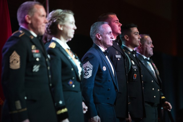 """Senior Enlisted Advisor to the Chairman of the Joint Chiefs of Staff Ramón """"CZ"""" Colón-López, center, stands at attention as medal citations are read for U.S. Army Sgt. Alec Rantanen, third from right, and Spc. Jesus Cruz, second from right, during the California Military Department Service Member of the Year Banquet, Jan. 18, 2020, in San Diego. The banquet recognized the best-enlisted Soldiers, Airmen and Sailors in the California Army National Guard, California Air National Guard and California State Guard. Rantanen earned Noncommissioned Officer of the Year honors for the California Army National Guard and Cruz was named Soldier of the Year. At right is Maj. Gen. David S. Baldwin, Adjutant General of the California Military Department."""