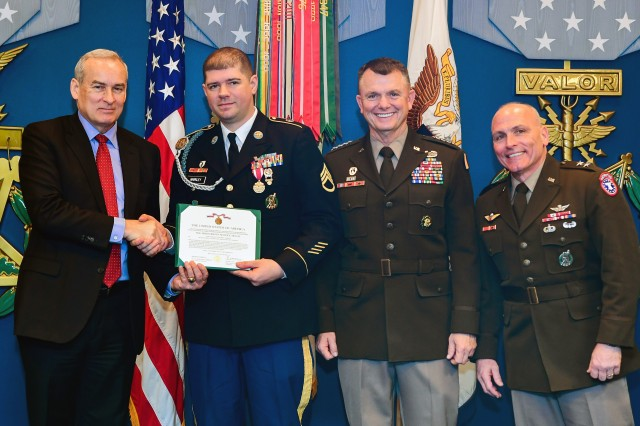 E. Casey Wardynski, left, assistant secretary of the Army for manpower and reserve affairs; Gen. Paul E. Funk II, commander of U.S. Army Training and Doctrine Command; and Maj. Gen. Frank Muth, commander of U.S. Army Recruiting Command, pose for a photograph with Staff Sgt. Leonard Markley, a recruiter assigned to the Cleveland Battalion in Toledo, Ohio. Markley and 15 other recruiters were recognized as the top recruiters of the first quarter of fiscal year 2020 during a ceremony at the Pentagon's Hall of Heroes in Arlington, Va., Jan. 22, 2020.