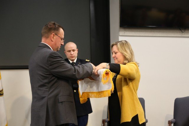 Dr. Donna Joyce, right, unfurls the scientific and professional flag, symbol of her executive status within the federal service, with the help of Dr. James Kirsch, during her appointment ceremony Jan. 21 at the U.S. Army Combat Capabilities Development Command Aviation & Missile Center at Redstone Arsenal, Ala. Joyce, who serves at the CCDC AvMC Software, Simulation, Systems Engineering and Integration Directorate, was appointed the senior research scientist for protective technologies effective Dec. 8.