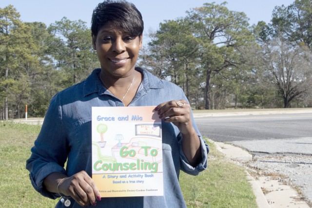 """Desiree Tomlinson, a retired Fort Jackson drill sergeant, holds the book she self wrote and published. The book """"Grace and Mia Go To Counseling,"""" is based on her daughters' experiences attending counseling during their parents divorce. The book helps dispel the fears of counseling for children coping with divorce."""