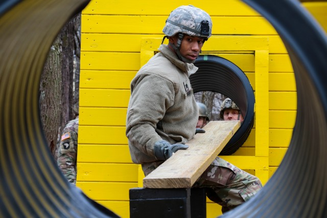 Lt. Col. Shaalim David, branch chief for casualty and mortuary affairs at U.S. Army Human Resources Command, relocates a plank on the double culvert obstacle to help his team overcome a challenge of the Leader Reaction Course during the Battalion Commander Assessment Program, Jan. 23, 2020, at Fort Knox, Ky.