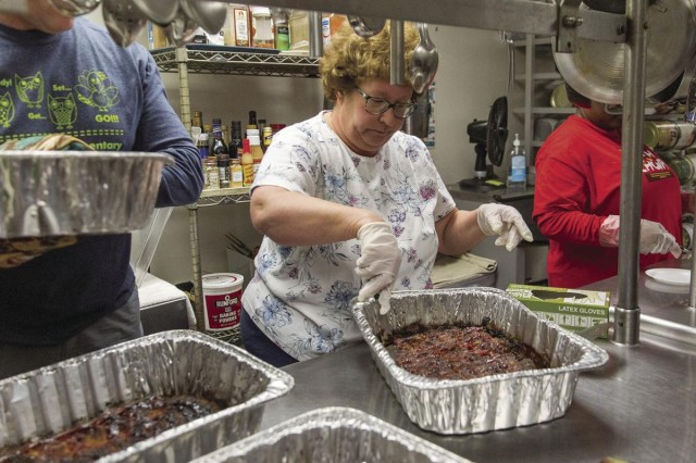 Sara Astrow, from the Fort Belvoir Jewish Community, slices meatloaf at the Elanor Kennedy homeless shelter.