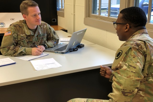 Capt. Stuart Denton, left, the officer in charge of the Joint Base Lewis-McChord Tax Center, goes over tax worksheets preparing for the opening of the tax season recently.
