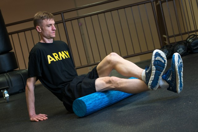 U.S. Army Maj. Timothy Benedict, an Army Public Health Center physical therapist, uses a foam roller massager to improve muscle tissue recovery following his workout on May 23, 2019.