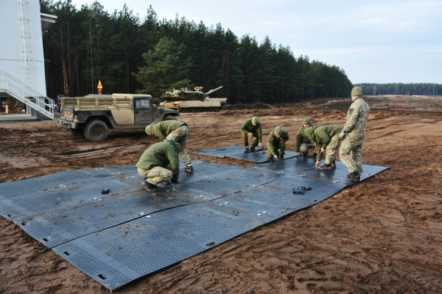 Service members from Lithuania assist the U.S. Soldiers by building flats for the tanks to drive on as part of trench clearing exercises on January 15, 2020, in Pabradé, Lithuania. Soldiers from the 1st Battalion, 9th Cavalry Regiment, 2nd Armored Brigade Combat Team, 1st Cavalry Division 'Headhunters', participated in the exercise to improve their skills at trench and obstacle clearing. (U.S. Army National Guard Photo by Staff Sgt. Scott D. Longstreet)
