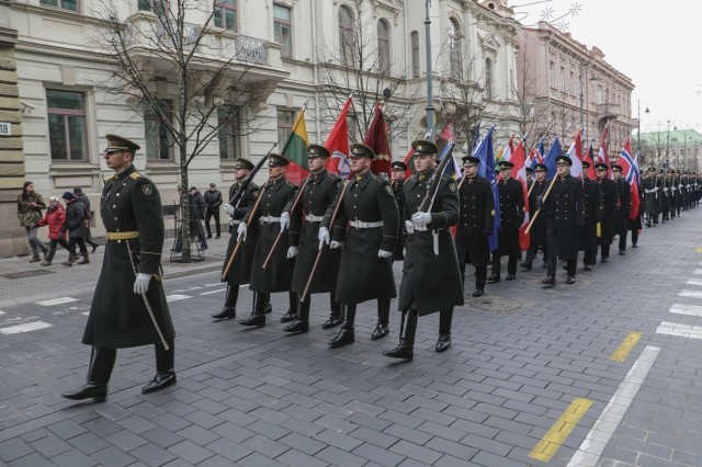 Lithuanian Armed Forces and divisions carry the flags of participating countries as they march in a national parade celebrating the 101st anniversary of the restored Lithuanian Armed Forces at Vilnius Cathedral Square on Nov 23, 2019. (U.S. Army photo by Staff Sgt. Greg Stevens)