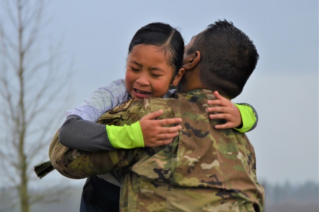 Tech. Sgt. Russell Dela Montanye of the 446th Logistics Readiness Flight hugs his daughter, Celine, during a surprise homecoming on the finish line of a 5K race hosted by I Corps and the 62nd Airlift Wing Jan. 24 to commemorate the life and legacy of Dr. Martin Luther King Jr. at Joint Base Lewis-McChord.
