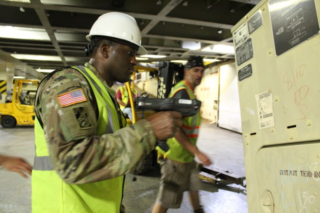 Staff Sgt. Deontre Austin, 599th operations NCO, scans data from a military shipping label during port operations on the M/V Cape Hudson at Pearl Harbor on Jan. 21.
