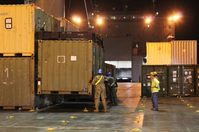 Navy cargo handling team personnel lower a container into place during port operations on the M/V Cape Hudson at Pearl Harbor on Jan. 21.