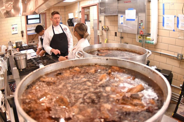 SSGs Justin Case and Erica Melendres, U.S. Army Culinary Team Members, discuss kitchen business during USACAT team preparations Jan. 24.