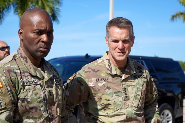 Army Maj. Gen. Antonio M. Fletcher, commanding general for Special Operations Command South, and Army Gen. Richard D. Clarke, U.S. Special Operations Command commander, honor Socsouth's fallen troops while observing the command's memorial wall during a visit to Homestead Air Reserve Base, Fla., Dec. 4, 2019.