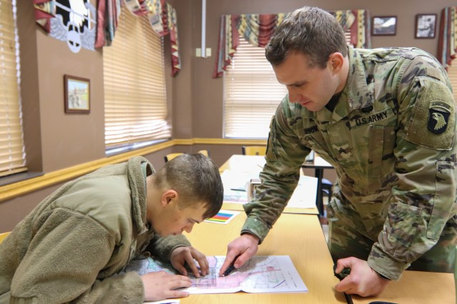 Sgt. Zachary Gibson(right), 227th Composite Supply Company, 129th Division Sustainment Support Battalion, 101st Airborne Division (Air Assault) Sustainment Brigade, helps Spc. William Cantrell, 74th Composite Truck Company, 129th Div. Sust. Support Bn 101st Abn. Div. (Air Assault) Sust. Bde., understanding map reading during a land navigation class that Gibson is leading.