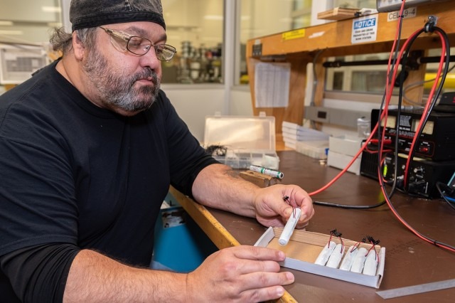 Electronics worker Joseph Crosby inspects finished batteries before affixing instruction labels. Crosby is one of five technicians who build more than 900 battery packs each month to power identify friend or foe transponders.