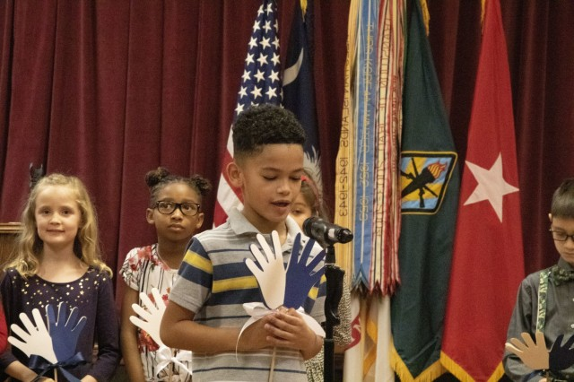 """C.C. Pinckney Elementary School students recite the """"I Have a Dream"""" speech by Dr. Martin Luther King Jr., Jan. 24 during the Martin Luther King remembrance luncheon at the NCO Club. The luncheon celebrated the life and deeds of King during the African American civil rights movement. Attendees of the luncheon were treated to several performances, lunch and a guest speaker who documented the movement in S.C. as a photographer."""
