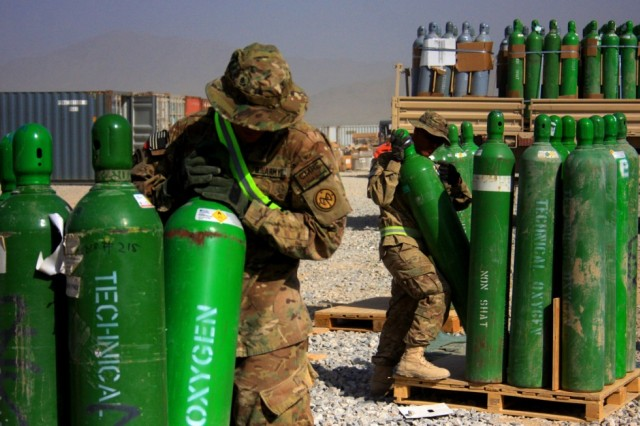 Sgt. Timothy Vandermied, from the 427th Brigade Support Battalion, and Spc. Michael Brunger, from the 1462nd Transportation Company, works on packaging oxygen cylinders that have accumulated in the Bagram Retrosort Yard into bundles for transportation on July 31, 20102. The Soldiers of HHC and B Company of the 427th were recently recognized with a Meritorious Unit Commendation for their work in conducting equipment retrieval and retrograde operations during this deployment.