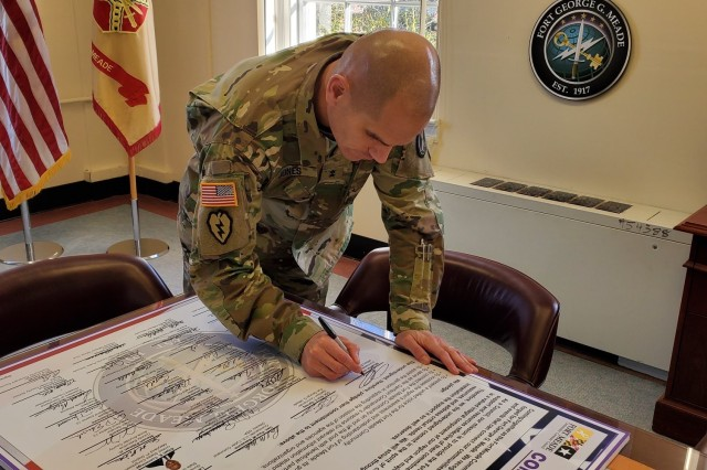 """Maj. Gen. Omar J. Jones IV, commanding general, Joint Force Headquarters - National Capital Region and the U.S. Army Military District of Washington, signs the Fort George G. Meade Community Covenant at the Housing Town Hall, January 21, 2020. The covenant is the guiding document for signatories who """"commit in the spirit of collaboration to build relationships, identify and combine resources, and address critical needs,"""" according to the document. The event brings together the community outside the fence line that supports Fort Meade."""