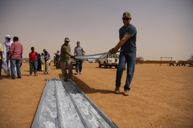 Airmen assigned to the 724th Expeditionary Air Base Squadron's civil engineer flight install tin roofing on a classroom at a village in Agadez, Niger, June 27, 2019. The airmen built the classroom using leftover construction materials from Air Base 201 and purchased tin for the roof locally.