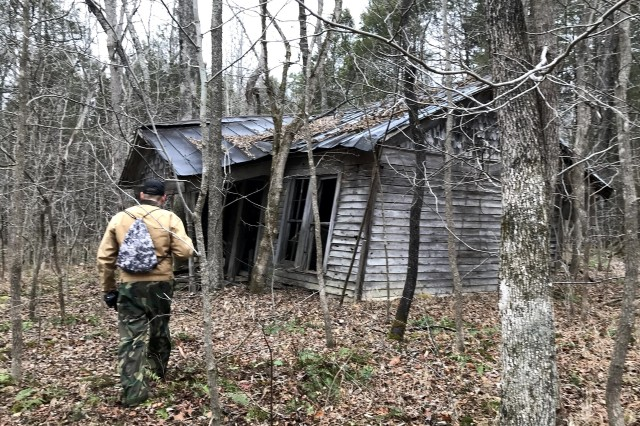 Matthew Rector, from the Fort Knox Cultural Resources Office, walks up to an old one-story house hidden in the woods in a live-fire impact area on the installation. The house, still standing after more than 80 years, was inspected by members of the post Environmental Management Division and Range Operations Section Jan. 2, 2020.