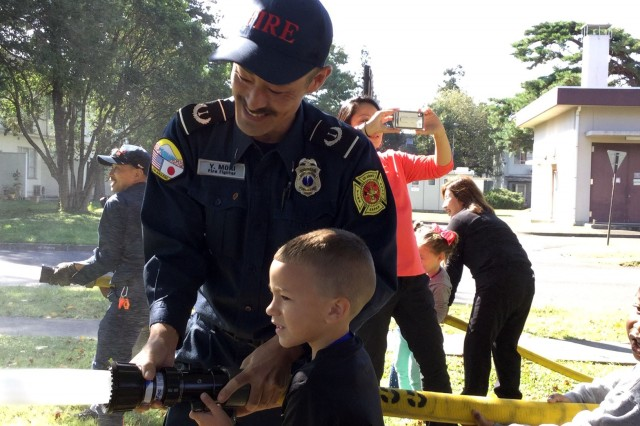 Yu Mori, a firefighter with U.S. Army Garrison Japan Fire and Emergency Services, shows a child how to spray a fire hose during a Fire Prevention Week event at John O. Arnn Elementary School, Sagamihara Family Housing Area, Japan, Oct. 9, 2019. Installation Management Command-Pacific named Mori the best civilian firefighter in the Pacific region.