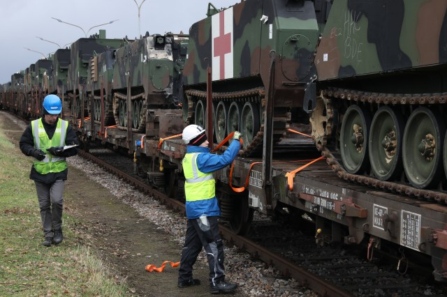 U.S. Army troop carrier vehicles get secured and tagged onto railcars as part of an Army prepositioned stock movement at Coleman Barracks in Mannheim, Germany, Jan. 28, 2020. This APS movement is the first movement of equipment in support of Defender-Europe 20.