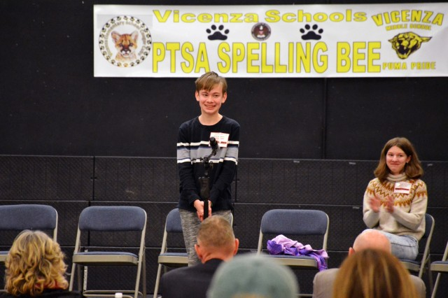 """VMS Eighth-grader Brandon Easler correctly spells """"impel"""", the last word at the 10th Vicenza Elementary/Middle School Spelling Bee Championship held in the VMS Multi-Purpose room Jan. 29. Easler placed third in the 2019 Spelling Bee Championship."""