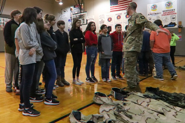 Pfc. Keneth Fouts, 74th Composite Truck Company, 129th Division Sustainment Support Battalion, 101st Airborne Division (Air Assault) Sustainment Brigade, shows students of Trigg County Middle School the different type of gear that 101st Airborne Division Soldiers wear such as wet weather gear, cold weather gear and operational camouflage pattern uniforms, Jan 28, in Cadiz, Ky.