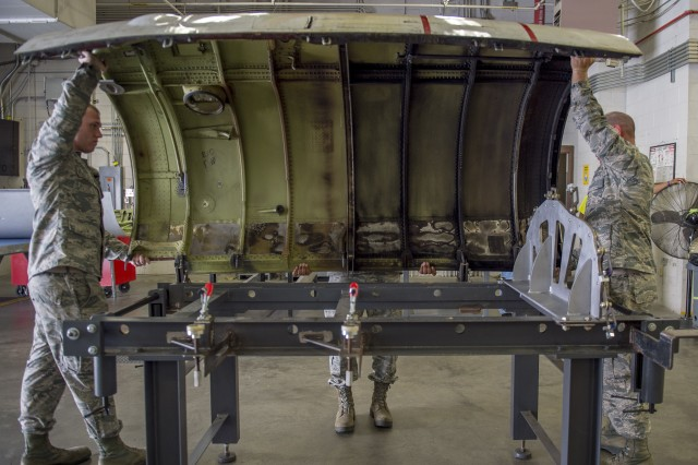 Sheet metal technicians with the Georgia Air National Guard's 116th Air Control Wing and the 461st Air Control Wing secure an engine aircraft cover on a cowling fixture table at Robins Air Force Base, Georgia, April 3, 2019. Maintainers with the wings designed the table, an innovative tool Air Force officials said will save the service about $500,000 a year.