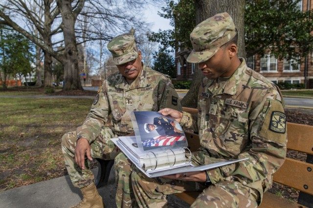 """Chief Warrant Officer 4 Phillip Brashear (left), a U.S. Army Reserve command chief warrant officer for the 80th Training Command, and his son, Tyler Brashear, an ROTC cadet at North Carolina A&T State University, flip through a binder of family photos while on a video production shoot for the Army Reserve in Greensboro, N.C., Jan. 16, 2020. Phillip Brashear is a helicopter pilot with combat experience and the son of Carl Brashear, the first African-American master diver in U.S. Navy's history who lost his leg during a tragic accident on a diver mission off the coast of Spain in 1966. Carl Brashear's life story about overcoming physical and racial adversity was featured in the Hollywood film """"Men of Honor"""" starring Cuba Gooding Jr. and Robert De Niro. Phillip Brashear has more than 38 years of military service between the U.S. Navy Reserve, the U.S. Army National Guard and the U.S. Army Reserve. He spent the majority of his Army career as a helicopter pilot with deployments to Bosnia and Iraq."""