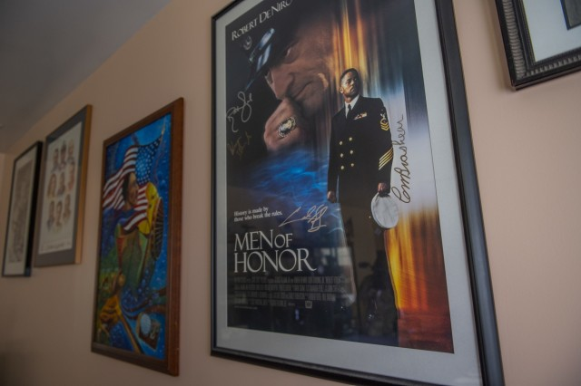 """A movie poster for """"Men of Honor"""" hangs next to other wall art in Phillip Brashear's home, a U.S. Army Reserve warrant officer, in memory of his father, Carl Brashear, the first African-American master diver in U.S. Navy's history who lost his leg during a tragic accident on a diver mission off the coast of Spain in 1966. Carl Brashear's life story about overcoming physical and racial adversity was featured in the Hollywood film """"Men of Honor"""" starring Cuba Gooding Jr. and Robert De Niro. His son, Phillip Brashear, has more than 38 years of military service between the U.S. Navy Reserve, the U.S. Army National Guard and the U.S. Army Reserve. He spent the majority of his Army career as a helicopter pilot with deployments to Bosnia and Iraq."""